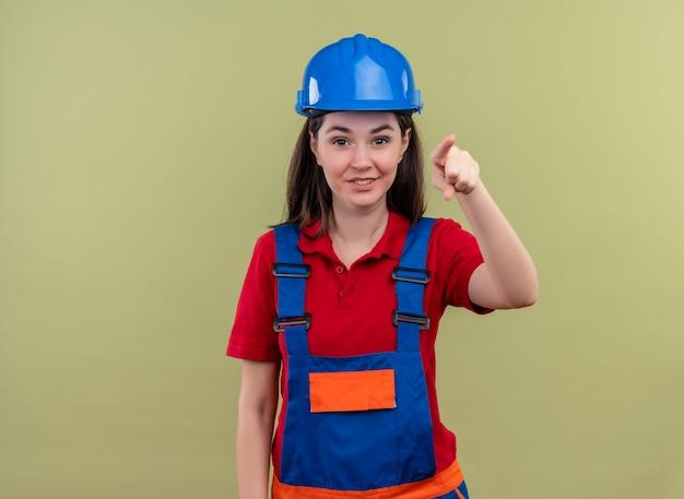 Glimlachend jong bouwersmeisje met blauwe veiligheidshelm wijst vooruit en bekijkt cameraon geïsoleerde groene achtergrond met exemplaarruimte