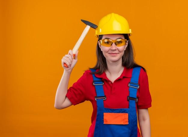 Glimlachend jong bouwersmeisje met veiligheidsbril houdt hamer tegen op geïsoleerde oranje achtergrond met exemplaarruimte