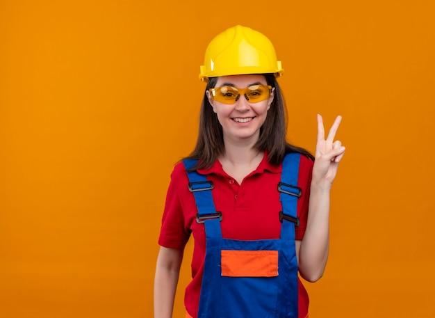 Glimlachend jong bouwersmeisje met veiligheidsbril toont het gebaar van de overwinningshand op geïsoleerde oranje achtergrond met exemplaarruimte