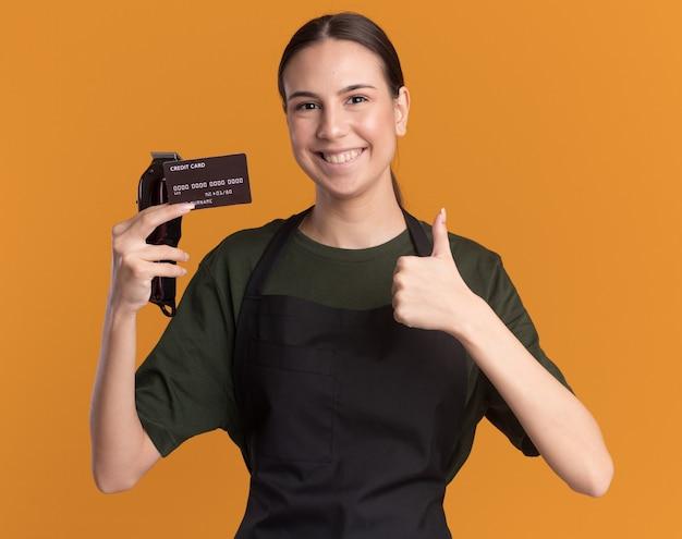 Glimlachend jong brunette kappersmeisje in uniform duimen omhoog met tondeuses en creditcard geïsoleerd op oranje muur met kopieerruimte