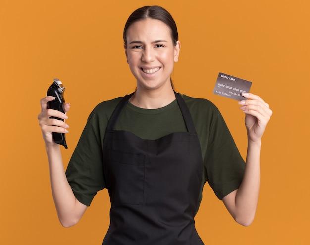 Glimlachend jong brunette kappersmeisje in uniform houdt tondeuses en creditcard geïsoleerd op een oranje muur met kopieerruimte