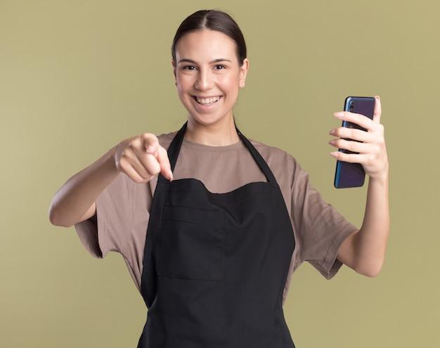 Glimlachend jong brunette kappersmeisje in uniform wijst naar de camera en houdt telefoon geïsoleerd op olijfgroene muur met kopieerruimte