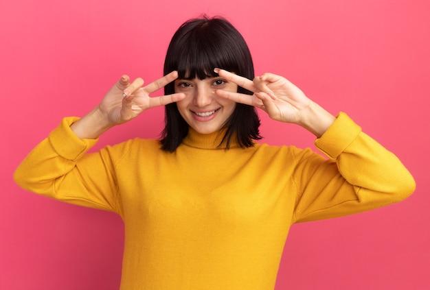 Glimlachend jong brunette kaukasisch meisje gebaren overwinning teken camera kijken door vingers geïsoleerd op roze muur met kopie ruimte