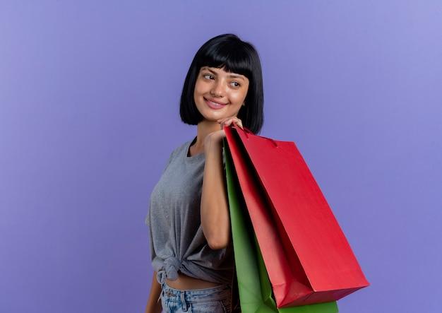 Glimlachend jong brunette kaukasisch meisje staat zijwaarts met veelkleurige boodschappentassen op schouder kijken naar kant