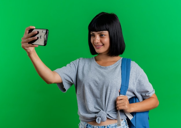 Glimlachend jong donkerbruin kaukasisch meisje die rugzak draagt kijkt naar telefoon die selfie neemt die op groene achtergrond met exemplaarruimte wordt geïsoleerd