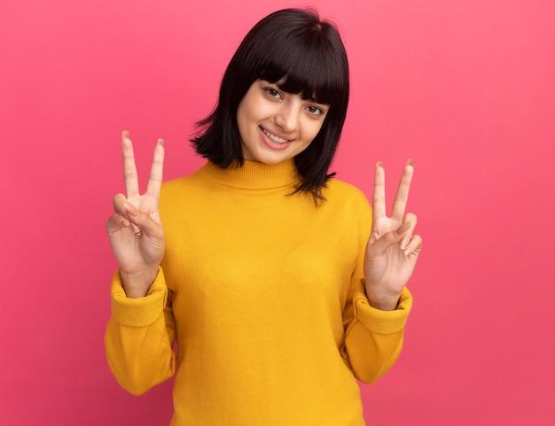 Glimlachend jong donkerbruin kaukasisch meisje gebaren overwinning handteken met twee handen