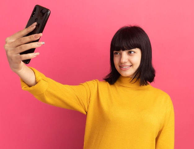 Glimlachend jong donkerbruin kaukasisch meisje houdt en kijkt naar telefoon die selfie op roze neemt