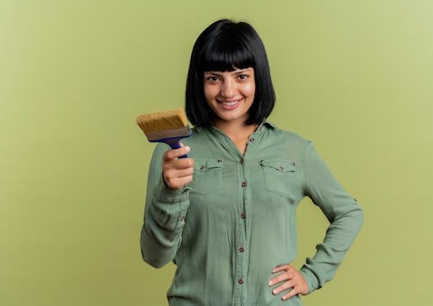 Glimlachend jong donkerbruin kaukasisch meisje legt hand op taille en houdt verfborstel die camera bekijkt die op olijfgroene achtergrond met exemplaarruimte wordt geïsoleerd