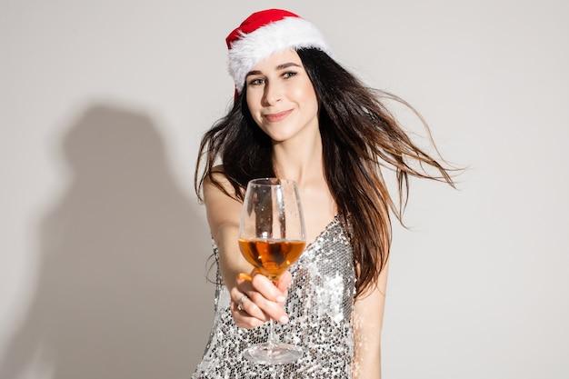 Glimlachend jong donkerbruin meisje in kerstmuts en zilveren feestelijke jurk vieren en suggereren glas champagne, kopieer ruimte.