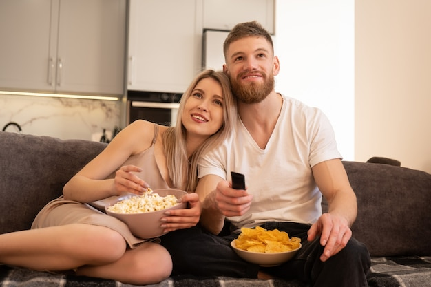 Glimlachend jong europees koppel zittend op de bank en tv of film kijken. man en meisje die chips en popcorn eten. vrije tijd en rust thuis. concept van samen genieten van tijd. interieur van studio appartement