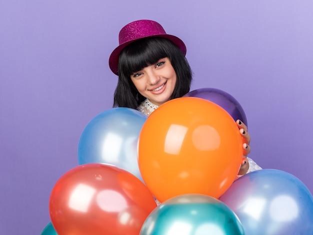 Glimlachend jong feestmeisje met een feesthoed die achter ballonnen staat en een geïsoleerd op een paarse muur aanraakt