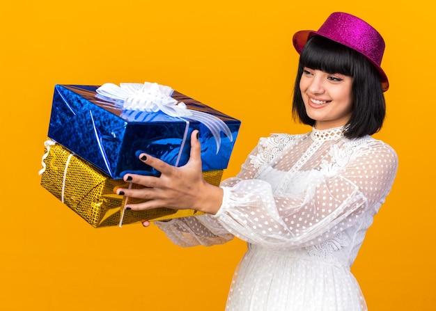 Glimlachend jong feestmeisje met een feesthoed die in profielweergave staat en cadeaupakketten uitrekt die naar hen kijken geïsoleerd op een oranje muur