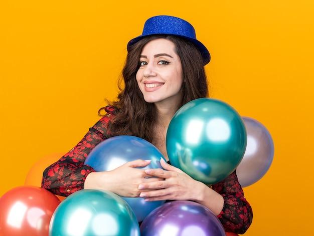 Glimlachend jong feestmeisje met een feestmuts die achter ballonnen staat en ze knuffelt terwijl ze naar een camera kijkt die op een oranje muur is geïsoleerd