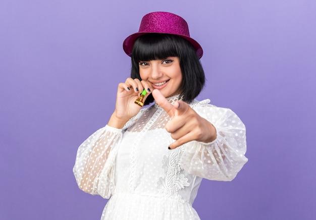 Glimlachend jong feestmeisje met feestmuts in profielweergave met feesthoorn kijkend en wijzend geïsoleerd op paarse muur