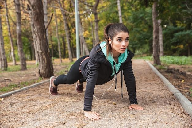 Glimlachend jong geschiktheidsmeisje die oefeningen doen in het park, planking