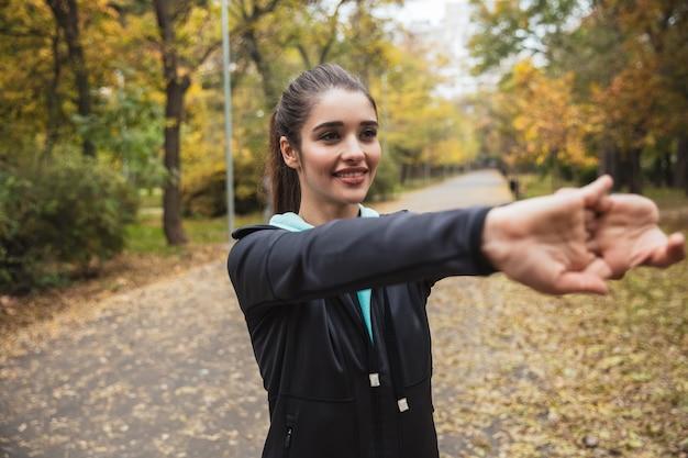 Glimlachend jong geschiktheidsmeisje die oefeningen doen in het park