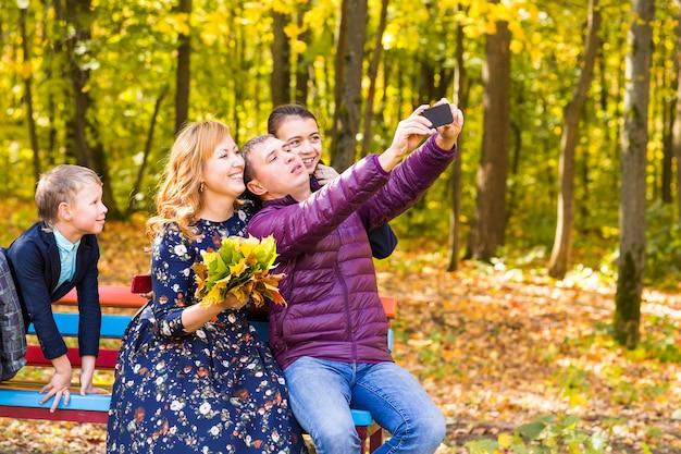 Glimlachend jong gezin selfies nemen op een herfstdag.