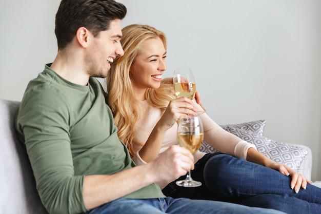 Glimlachend jong houdend van paar die champagne van de alcohol de witte wijn drinken.