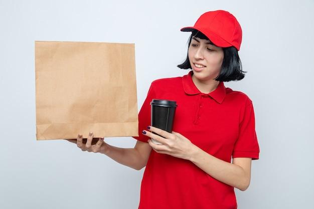 Glimlachend jong kaukasisch bezorgmeisje dat een papieren beker vasthoudt en naar voedselverpakkingen kijkt