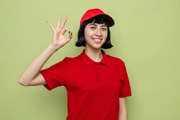 Glimlachend jong kaukasisch bezorgmeisje dat ok teken gebaart