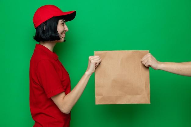 Glimlachend jong kaukasisch bezorgmeisje dat papieren voedselverpakkingen aan iemand geeft