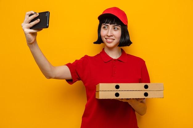Glimlachend jong kaukasisch bezorgmeisje dat pizzadozen vasthoudt en selfie op de telefoon neemt