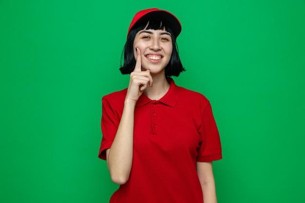 Glimlachend jong kaukasisch bezorgmeisje dat vinger op haar gezicht legt en
