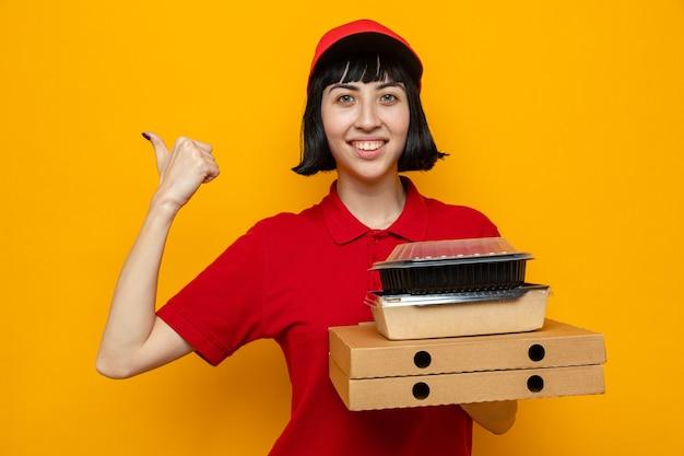 Glimlachend jong kaukasisch bezorgmeisje dat voedselcontainers vasthoudt met verpakking op pizzadozen en naar de zijkant wijst