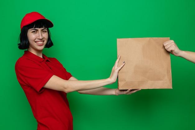 Glimlachend jong kaukasisch bezorgmeisje dat voedselverpakking geeft aan iemand die naar voren kijkt