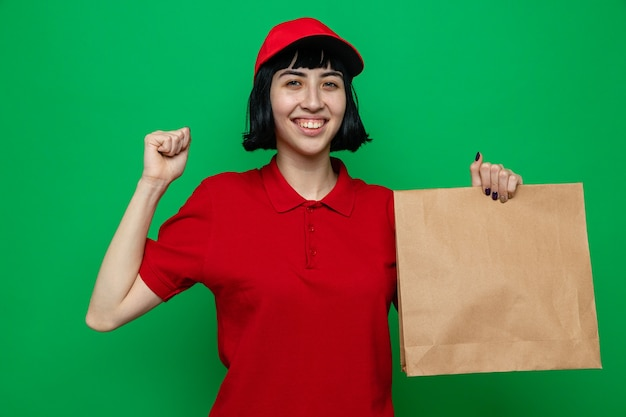 Glimlachend jong kaukasisch bezorgmeisje dat voedselverpakking vasthoudt en vuist houdt