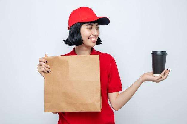 Glimlachend jong kaukasisch bezorgmeisje dat voedselverpakkingen vasthoudt en naar een papieren beker kijkt