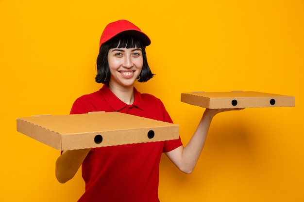 Glimlachend jong kaukasisch bezorgmeisje met pizzadozen op handen