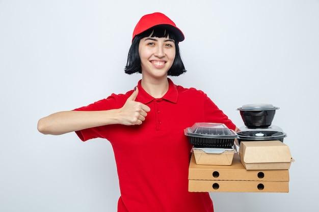 Glimlachend jong kaukasisch bezorgmeisje met voedselcontainers en verpakkingen op pizzadozen die omhoog duimen