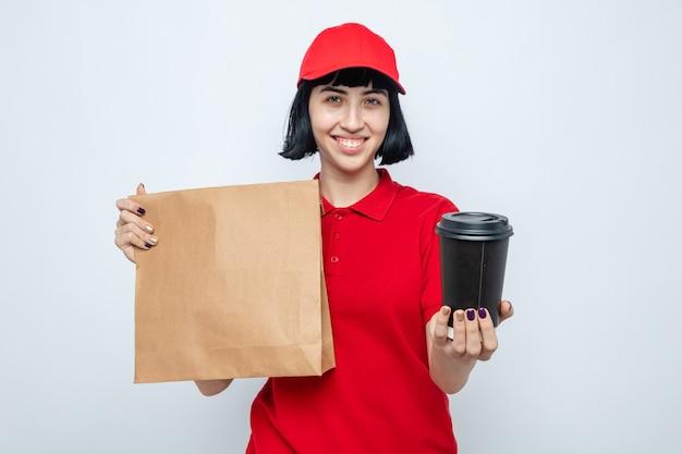 Glimlachend jong kaukasisch bezorgmeisje met voedselverpakking en papieren beker kijkend naar de voorkant