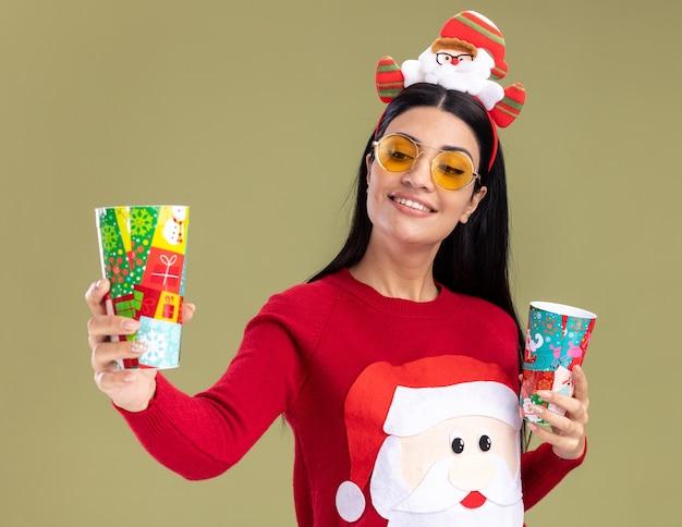 Glimlachend jong kaukasisch meisje dat de hoofdband van de kerstman en trui met glazen draagt die plastic kerstmisbekers uitrekken houdt die het bekijken bekijken geïsoleerd op olijfgroene achtergrond
