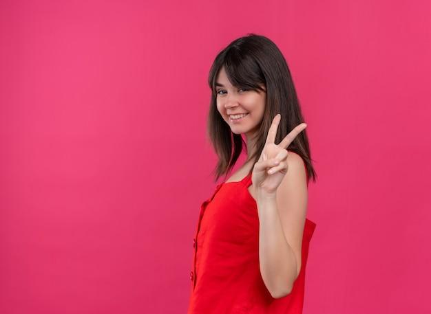 Glimlachend jong kaukasisch meisje dat het gebaar van de overwinningshand doet en camera op geïsoleerde roze achtergrond met exemplaarruimte bekijkt