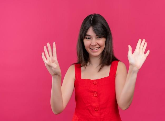 Glimlachend jong kaukasisch meisje dat negen met vingers toont en cameraon geïsoleerde roze achtergrond bekijkt