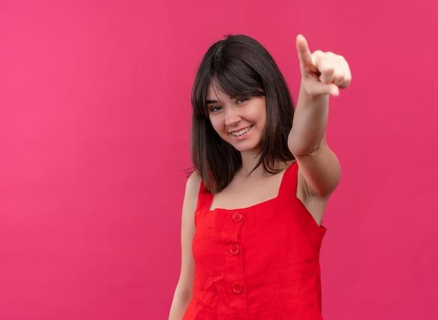 Glimlachend jong kaukasisch meisje dat vooruit op geïsoleerde roze achtergrond met exemplaarruimte richt