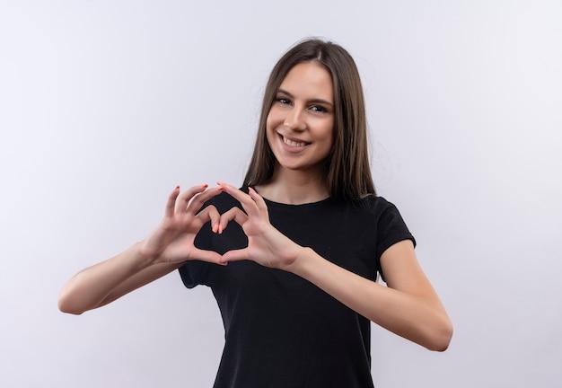 Glimlachend jong kaukasisch meisje dat zwarte t-shirt draagt die hartgebaar op geïsoleerde witte achtergrond toont