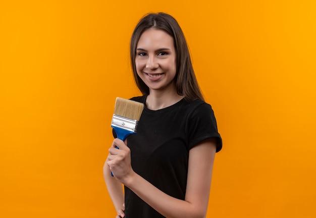 Glimlachend jong kaukasisch meisje die de zwarte verfborstel van de t-shirtholding op geïsoleerde oranje achtergrond dragen