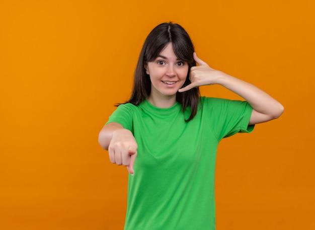 Glimlachend jong kaukasisch meisje in groen overhemd roept gebaar en wijst op camera op geïsoleerde oranje achtergrond