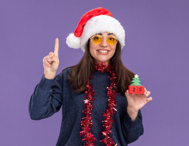 Glimlachend jong kaukasisch meisje in zonnebril met kerstmuts en slinger om nek houdt kerstboom ornament en wijst omhoog geïsoleerd op paarse muur met kopie ruimte