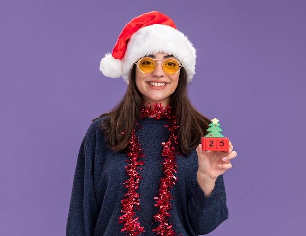 Glimlachend jong kaukasisch meisje in zonnebril met kerstmuts en slinger om nek houdt kerstboom ornament geïsoleerd op paarse muur met kopie ruimte