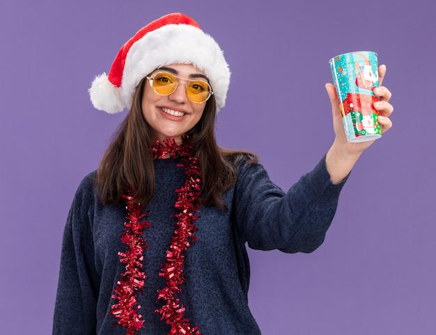 Glimlachend jong kaukasisch meisje in zonnebril met kerstmuts en slinger om nek houdt papieren beker geïsoleerd op paarse muur met kopieerruimte