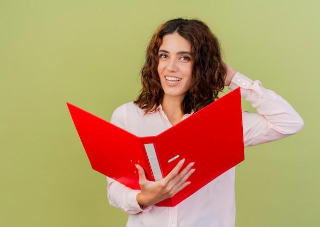 Glimlachend jong kaukasisch meisje legt hand op hoofd achter het houden van bestandsmap en kijken naar camera geïsoleerd op groene achtergrond met kopie ruimte