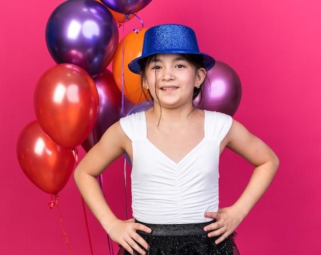 Glimlachend jong kaukasisch meisje met blauwe feestmuts die handen op de taille legt en voor heliumballonnen staat geïsoleerd op roze muur met kopieerruimte