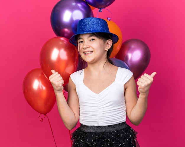 Glimlachend jong kaukasisch meisje met blauwe feestmuts die voor heliumballonnen staat en omhoog wijst geïsoleerd op roze muur met kopieerruimte