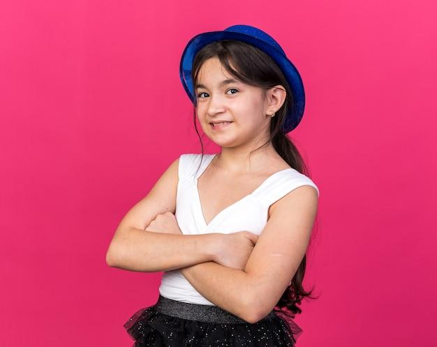 Glimlachend jong kaukasisch meisje met blauwe feestmuts die zich met gekruiste wapens bevindt die op roze muur met exemplaarruimte worden geïsoleerd