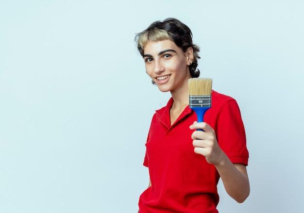 Glimlachend jong kaukasisch meisje met de kwast van de de holdingsverf van het pixiekapsel op witte achtergrond met exemplaarruimte wordt geïsoleerd