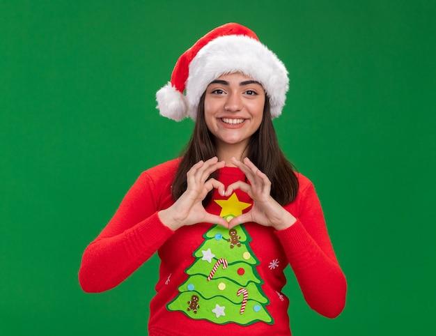 Glimlachend jong kaukasisch meisje met het teken van het de gebarenhart van de santahoed dat op groene achtergrond met exemplaarruimte wordt geïsoleerd